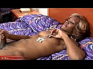 Black tranny jerks off on the bed and takes a facial cumshot